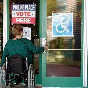 A female voter in a wheelchair opens an accessible door to a polling place
