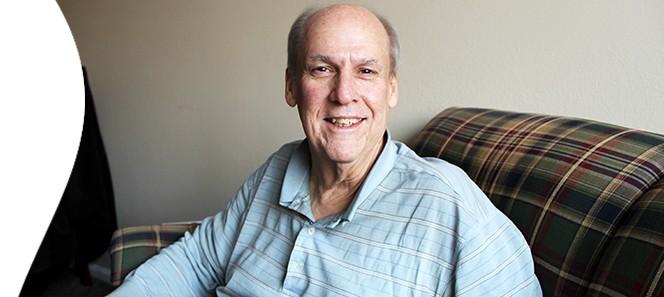 Jeffrey Burkhart smiles fora photograph in his new apartment