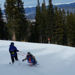 Ty Smith skis downhill with adaptive ski equipment