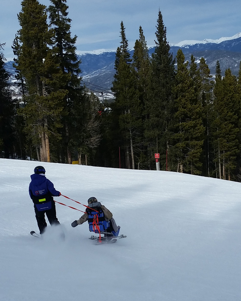 Ty Smith skis downhill with adaptive ski equipment