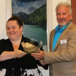 Angie Tenorio and Billy Allen smile for the camera holding the Susan J Elliott Award for Outstanding Service