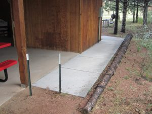 New concrete ramp leading to covered picnic pavilion with small portion of red and black picnic table showing.