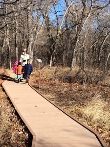 Bear Creek Nature Center Songbird Trail with a woman and three young children walking towards the camera on the trail