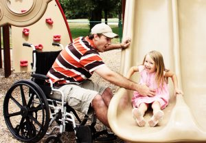 Man using wheelchair playing with little girl