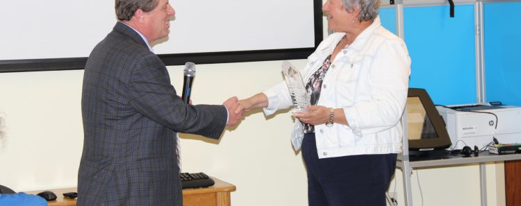 Clerk and Recorder, Chuck Broerman, presents the Stars and Stripes award to Patricia Yeager