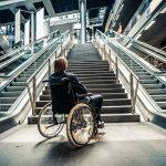Person in wheelchair looking up a flight of stairs