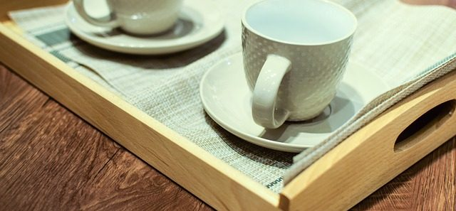 Two cups and saucers on a tray waiting to have coffee poured into them.