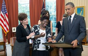 Lois Curtis, the plaintiff in Olmstead v. L.C., (center) presents President Barack Obama with a self-portrait of herself as a child that she painted.