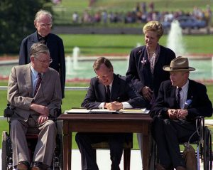 President Bush signs the Americans with Disabilities Act on the South Lawn of the White House. Sharing the dais with the President and he signs the Act are (standing left to right): Rev. Harold Wilkie of Clairmont, California; Sandra Parrino, National Council on Disability; (seated left to right): Evan Kemp, Chairman, Equal Opportunity Commission; and Justin Dart, Presidential Commission on Employment of People with Disabilities. Mrs. Bush and Vice President Quayle participate in the Ceremony.