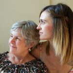 Woman and her daughter sit closely and look out a sunny window together