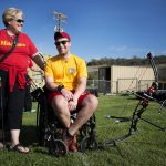 Marine veteran Cpl. Richard Stalder smiles with sunglasses on and looking at the camera while seated in his wheelchair outside on a sunny day with his archery kit. He is accompanied by his mother, who is standing to his left, with sunglasses on and looking at him.