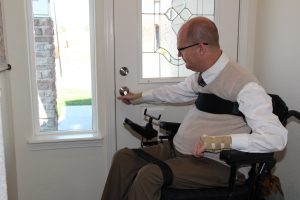 Photo of Jeremy using the lever handle to open the door.