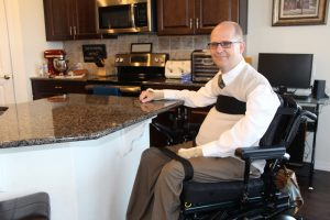Photo of Jeremy Chatelain sitting at his kitchen counter that was designed to be low enough for access.