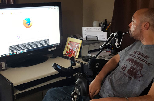 Man in wheelchair using a puff/blow device to control a computer