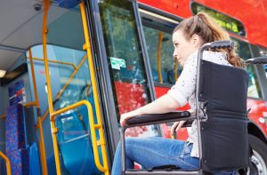 Woman in wheelchair getting on bus