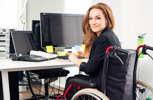 Woman sitting in front of a computer in a wheelchair