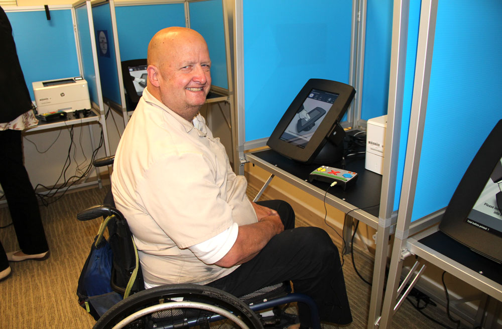 Man in wheelchair in voting booth