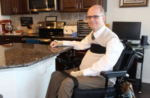 Man sitting in his kitchen in a power chair