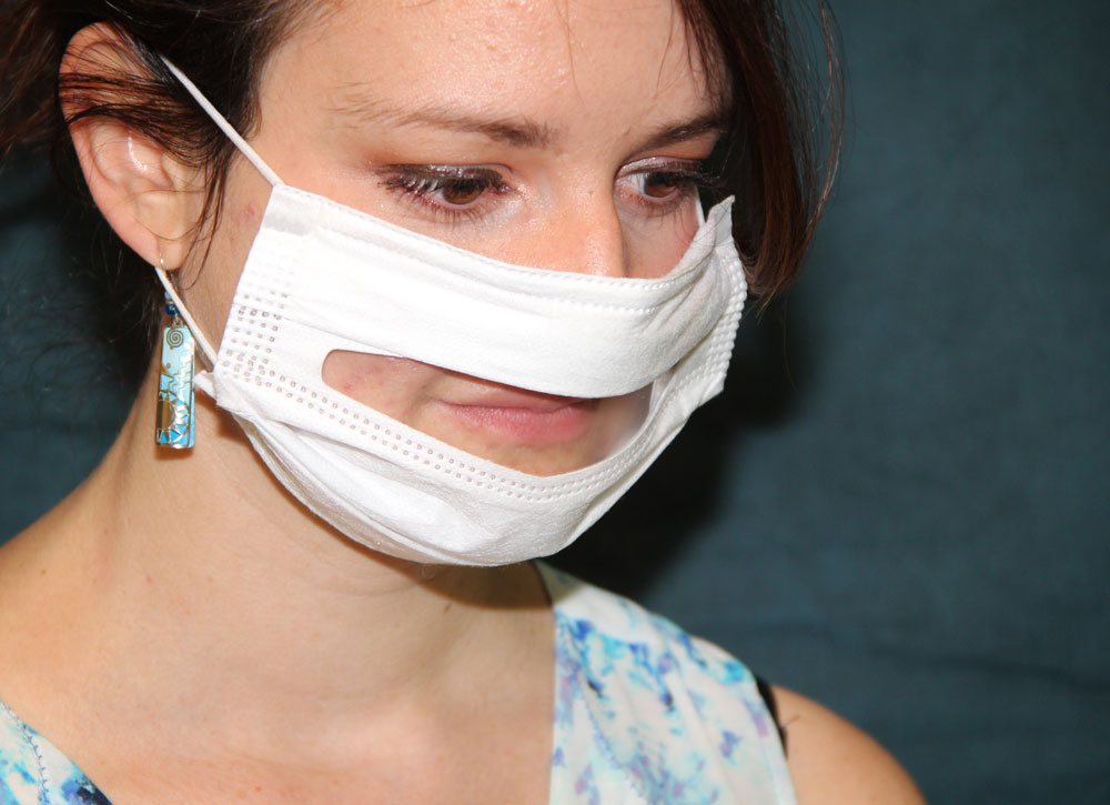 Woman wearing medical exam face mask with transparent sheet covering her lips so people who are Deaf or hard of hearing can see her lips moving when she speaks