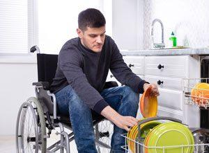 Man in wheelchair loading a dish washing machine