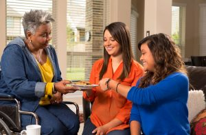 Woman offering cookies to two younger women