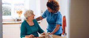 In-home care provider helping elderly client eat