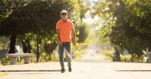 Blind man walking through park with white cane