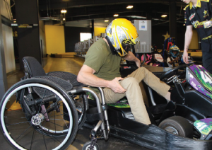 Photo of man transferring from wheelchair to adaptive go-kart