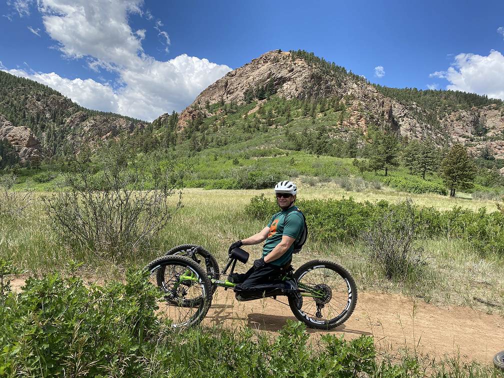 Drew Wills sitting on handcycle on trail